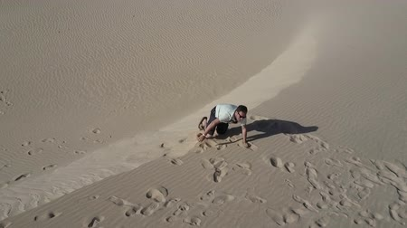 Man struggling to climb desert sand dune lays on his back at the top. Aerial shot. High angle view. Stok Video