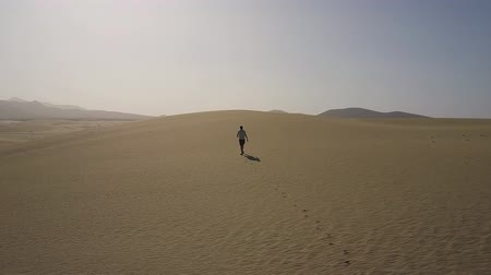 Man walking in desert establishing shot. Drone shot. Stok Video
