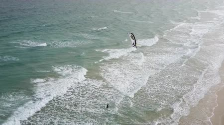 Kitesurfer entering ocean waters. Drone panorama of ocean waves splashing on beach sands.