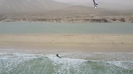 Kitesurfer surfing in ocean waters. Drone panorama of ocean and desert mountains.