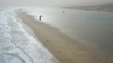Sandy isthmus in Fuerteventura, Canary Islands. Kitesurfer kites dot the sky like birds. Drone shot.