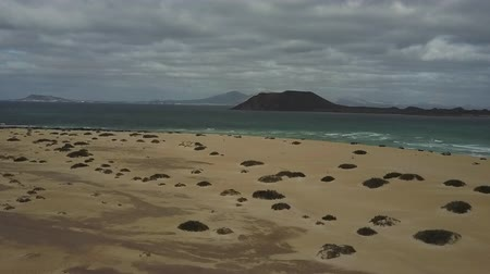 Beach sands and an overcast sky above ocean waters. Mountains in the distance. Drone shot.