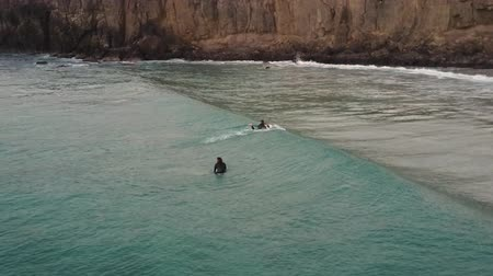 vanishing point : Surfers in the waters of the Atlantic Ocean, near the coast of Fuerteventura, Canary Islands, Spain.