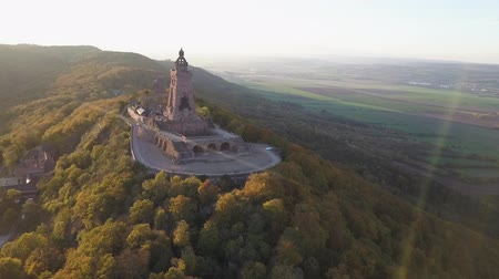 william : Aerial panorama of the Kyffhauser monument and the landscape beyond. Lens flare appearing from the sunny sky. Drone shot.