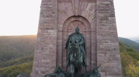 william : Ascending drone shot of the Kyffhauser monument in Thuringia, Germany. Mountains sunny panorama stretches out above and beyond.