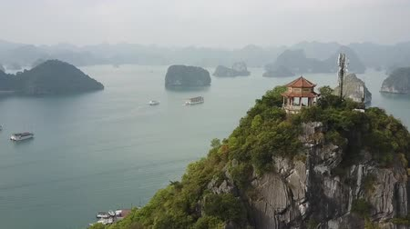 不思議 : Birds eye view of Ha Long Bay, Vietnam, with a gazebo atop a hill. Limestone karst islands spread out over the horizon while tourist cruise boats sail below. Drone shot. 動画素材