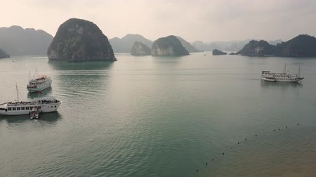 Beach in Ha Long Bay Vietnam. Panorama of Karst islands and cruise ships in the waters. Drone shot.