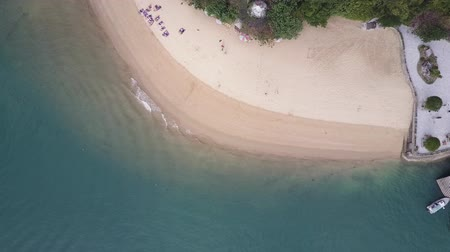 ha : Tropical beach overhead aerial. Calm waters gently rolling towards beach sands. Drone shot. Overhead shot.