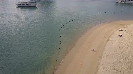 Man swimming past the buoys towards a cruise ship. Drone shot of a beach and the waters of Ha Long Bay, Vietnam. Stok Video