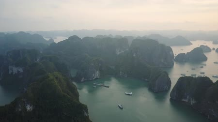 ha : Karst mountain formations and tourist cruise ships in the waters of Ha Long Bay, Vietnam. Drone shot. Stock Footage