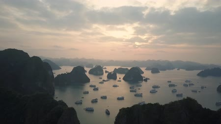 Throngs of ships and karst rock formations dotting the waters of Ha Long Bay, Vietnam, at sunset. Drone shot.