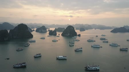 tourist silhouette : Ships in Ha Long Bay, Vietnam, surrounded by karst island hills. Drone shot. Stock Footage
