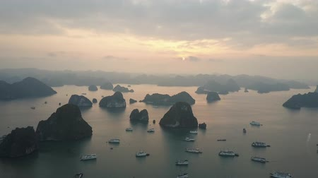 Multitude of cruise ships in Ha Long Bay, Vietnam, surrounded by karst island hills. Sun setting over distant horizon. Drone shot.