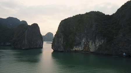 Karst mountains in Ha Long Bay, Vietnam. Cruise ships sailing amidst in the rocks. Drone shot.