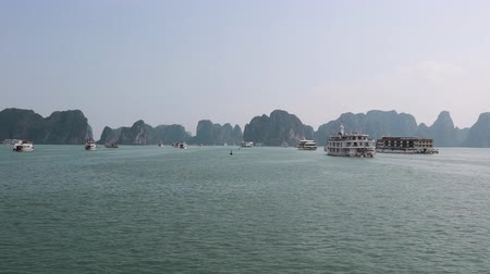 sail rock : Sightseeing cruise boats sailing in front of the karst formations of Ha Long Bay, Vietnam. Long shot.