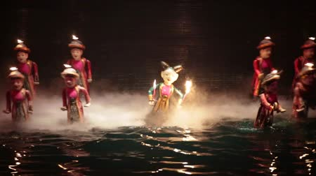Vietnamese water puppetry show. A demon holding a flame and fire holding men. Stok Video