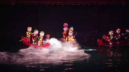 Vietnamese water puppetry show. Soldiers on boats face a sea monster. Stok Video