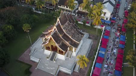 Haw Pha Bang temple in Luang Prabang to the sun setting over the Mekong river. Drone shot.