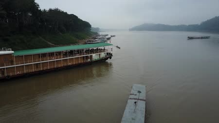 The Mekong River in Laos, near Luang Prabang. Sightseeing boats sailing on a cloudy day. Drone shot. Stok Video