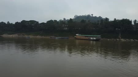 rowboat : The Mekong River in Laos, near Luang Prabang. Tourist boats and a rowboat sailing on a cloudy day. Drone shot.