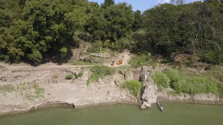 prabang : Group of monks walking on the sandy banks of a river in Laos. Aerial view. Profile view. Stock Footage