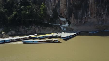 The entrance of the Pak Ou Caves on the Mekong River. Sightseeing tour boats lined up in the front. Drone Shot. Stok Video