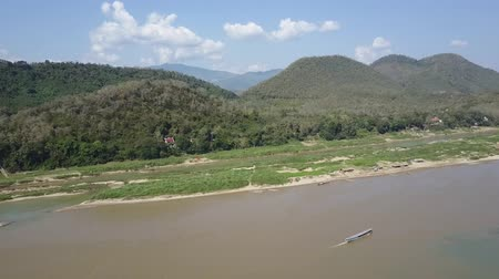 Mountainous landscape with lush vegetation along the shores of the Mekong River in Laos. Drone shot.