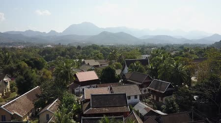 Flying over tropical suburban housing in Luang Prabang, Laos. Palm trees and house rooftops with silhouettes of mountains in the distant horizon. Aerial shot. Panorama.