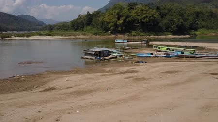 boathouse : Sandy river shores of the Mekong River in Laos. Boatmen working in the distance. Wide shot. Stock Footage