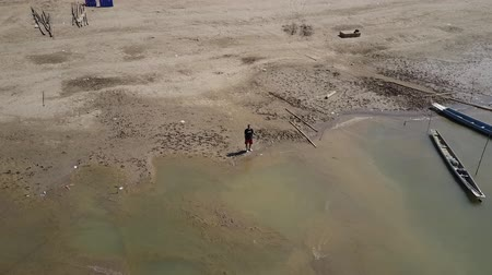 the mekong : Man standing on the shores of the sandy beaches of the Mekong River in Laos. Arc shot. Drone shot. Stock Footage