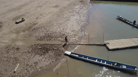 boathouse : Man jogging on the shores of the sandy beaches of the Mekong River in Laos. Drone shot.