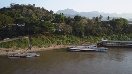 verdant : Aerial view of the shores of the Mekong River at Luang Prabang. City street traffic along the shore and silhouettes of mountains in the distance. Stock Footage