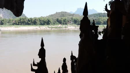 prabang : Standing Buddha statues silhouettes inside the shrine of the Pak Ou Caves in Laos. The Mekong River flowing in the background.