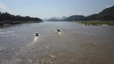 vanishing point : Two boats sail down the Mekong River in Luang Prabang, Laos. Aerial shot. Vanishing point.