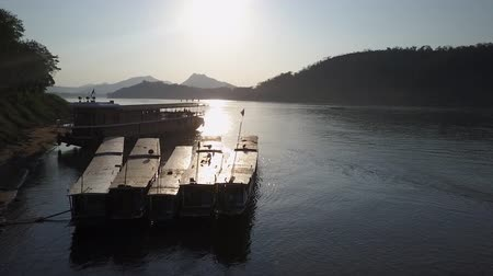shores : Sunshine over boats and the waters of the Mekong River. Aerial shot.