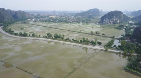 ninh : Landscape aerial of rice fields in rural Ninh Binh, Vietnam. Houses in the distance below. Establishing shot. Aerial shot.