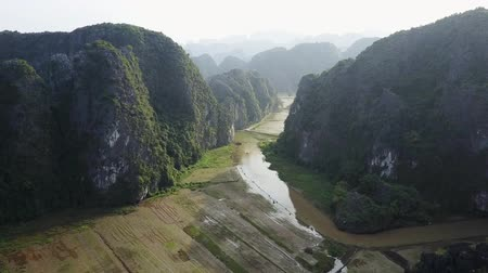 tam coc caves : Birds eye view aerial of river valley in Ninh Binh Vietnam. Mountain silhouettes stretch out in the distance horizon. Drone shot. Stock Footage