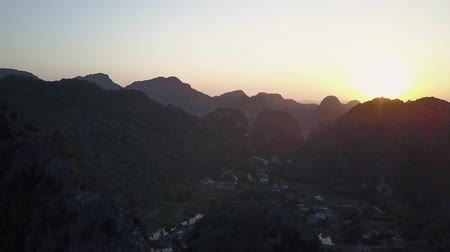 ninh : Sun setting over the mountainous landscape of Ninh Binh, Vietnam. Houses nestled in-between the steep rock precipices. Aerial shot. Panorama.