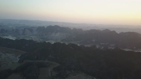 esneme : Sun setting over the mountainous landscape of Ninh Binh, Vietnam. Houses nestled in-between the steep rock precipices and small cities stretch out on the ground . Aerial shot. Panorama. Stok Video