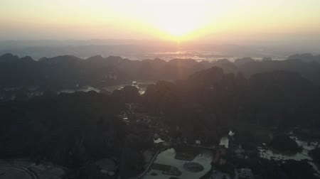 tourist silhouette : Sun setting over the mountainous landscape of Ninh Binh, Vietnam. Houses nestled in-between the steep rock precipices. Aerial view. Panorama. Stock Footage