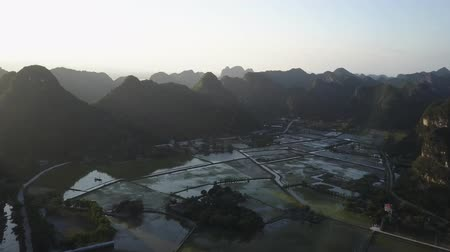 ninh : Sunrise over a mountainous landscape with a valley of rice fields, in Ninh Binh, Vietnam. Aerial shot.