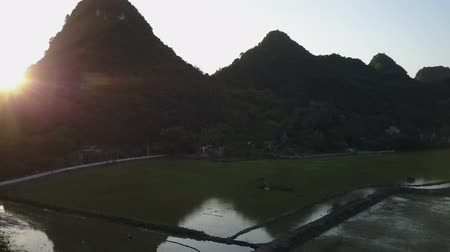 ninh : Turning away from the sunrise in a mountainous region in rural Ning Binh, Vietnam. Drone shot.