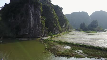 tam coc caves : Flying above a calm river between karst mountains in Vietnam. Rowing boats gently glide down below. Aerial shot. Stock Footage