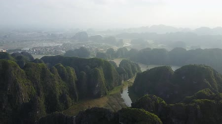 ninh : The limestone mountains of Ninh Binh filmed from the air. Silhouettes of mountain peaks in the horizon and a city far below. Aerial shot.