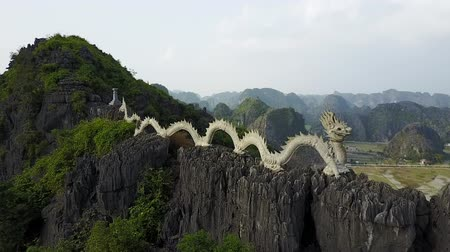 ninh : The lying dragon stature in Ninh Binh Vietnam. Mountains stretch out in the horizon beyond. Drone shot.