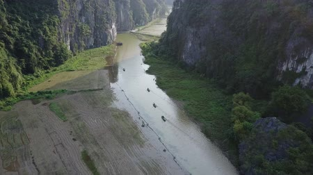 tam coc caves : Vietnamese tour boats rowing passengers along the Tam Coc River in Ninh Binh, Vietnam. Overhead shot. Drone shot.