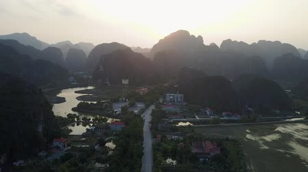 vanishing point : Rural community in Ninh Binh, Vietnam. Mountain Silhouettes cover the background. Establishing shot. Aerial shot. Pull back shot.