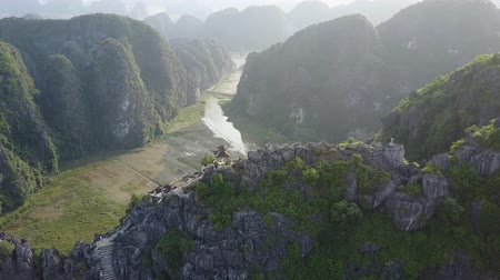 ninh : Aerial panorama of mountainous landscape in Ninh Binh, Vietnam. Tourist stand atop the mountain peaks. Drone shot. Stock Footage