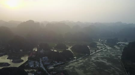 ninh : Vietnamese countryside landscape filmed from a slowly ascending drone. Spectacular mountain silhouettes loom over the valley underneath. Aerial shot. Extreme wide panorama.