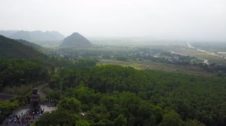 ninh : Laughing Buddha statue and the surrounding landscape in Ninh Binh, Vietnam. Aerial shot. Establishing shot.